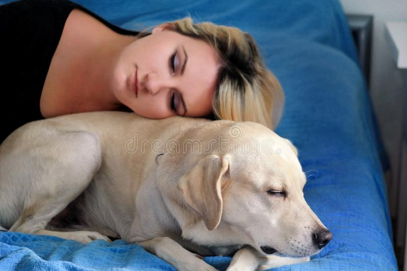 Woman with cute dogs at home. Handsome girl resting and sleeping with her dog in bed in bedroom. Owner and dog sleeping in sofa. stock photography