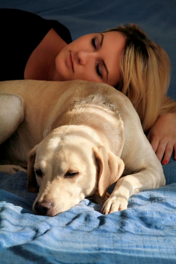 Woman with cute dogs at home. Handsome girl resting and sleeping with her dog in bed in bedroom. Owner and dog sleeping in sofa. stock photos
