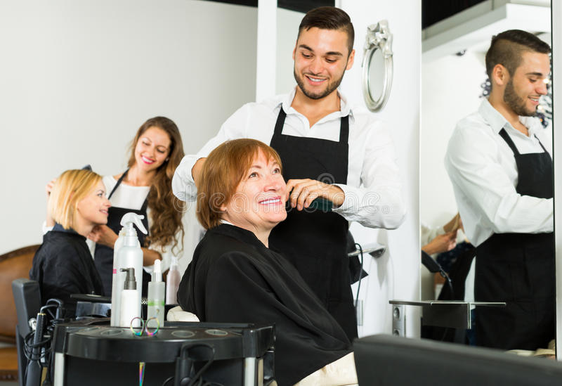 Woman cuts hair at the hair salon. Elderly women cuts hair at the hair salon and smiling royalty free stock images