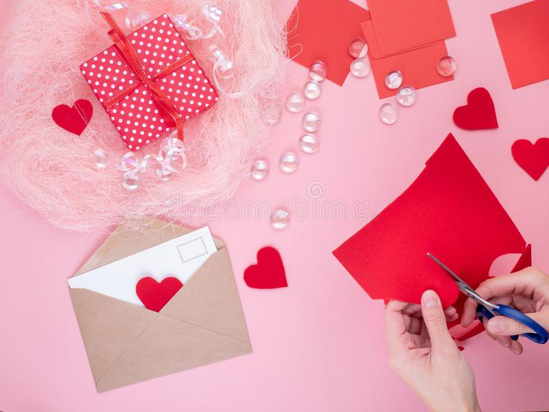 Woman cuts out red felt hearts, homemade crafts for Valentine`s. Day, hand made creativity, top view royalty free stock images