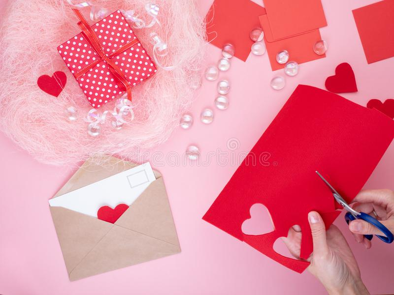 Woman cuts out red felt hearts, homemade crafts for Valentine`s. Day, hand made creativity, top view royalty free stock photography