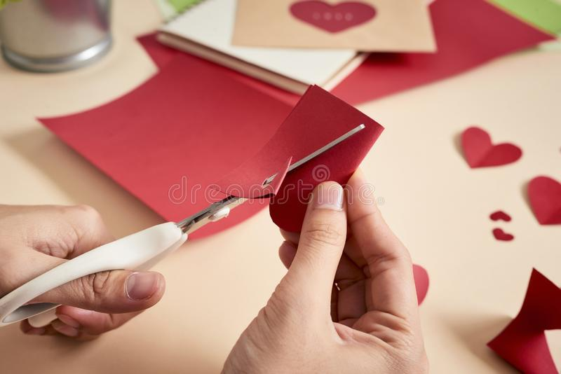 woman cuts out red felt hearts, homemade crafts for Valentine`s day, hand made creativity. royalty free stock photo