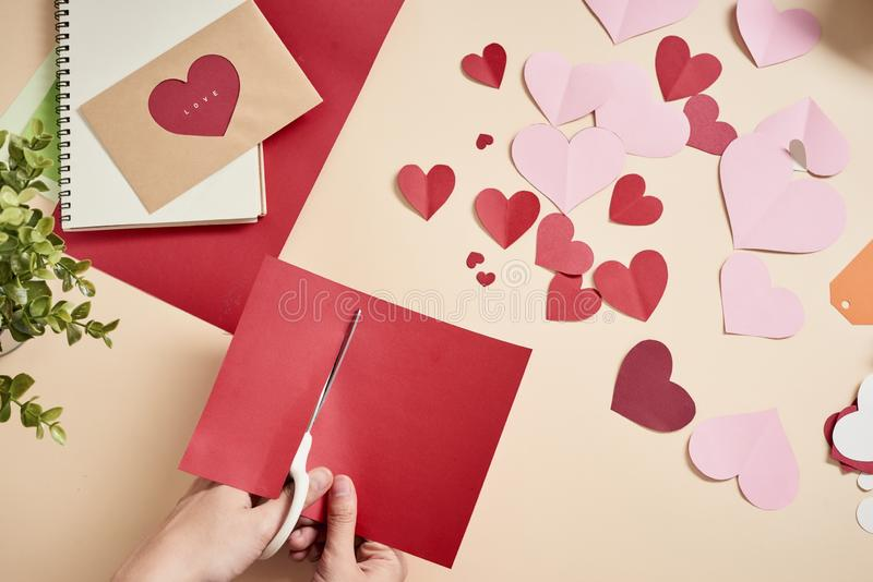 Woman cuts out red felt hearts, homemade crafts for Valentine`s day, hand made creativity, top view.  royalty free stock images