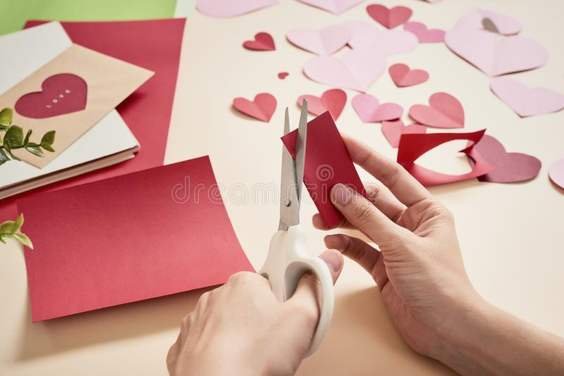 Woman cuts out red felt hearts, homemade crafts for Valentine`s day, hand made creativity, top view.  royalty free stock photos