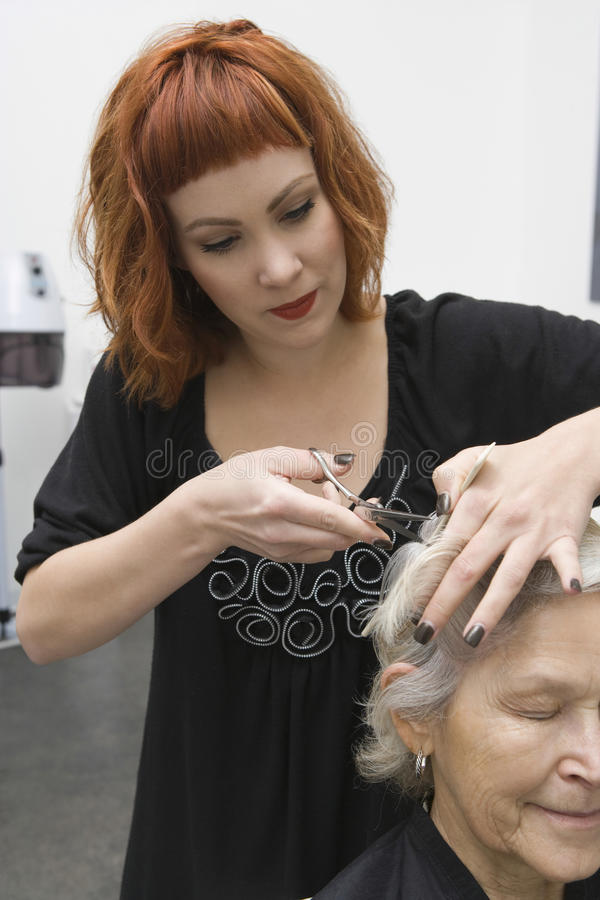 Woman Cutting Female Client's Hair In Salon royalty free stock photography