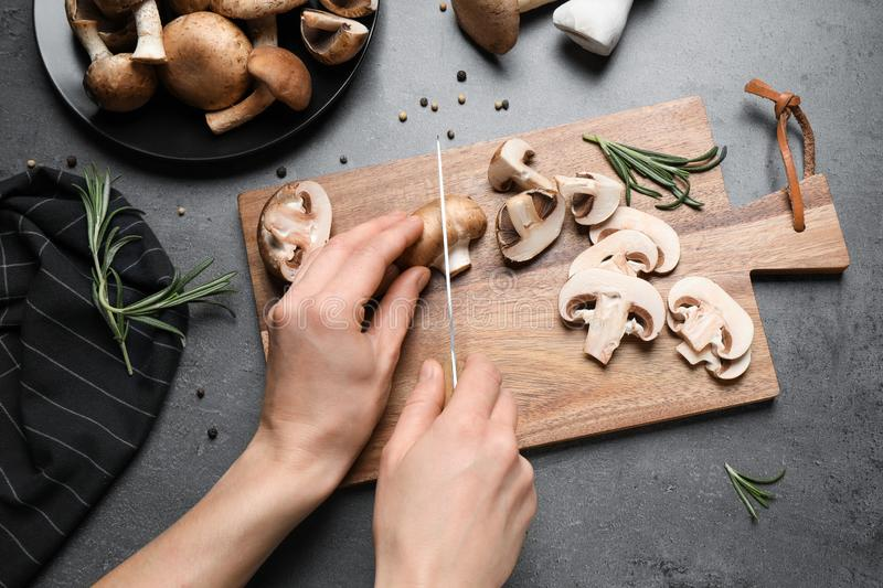 Woman cutting fresh wild mushrooms at grey, top view stock photo