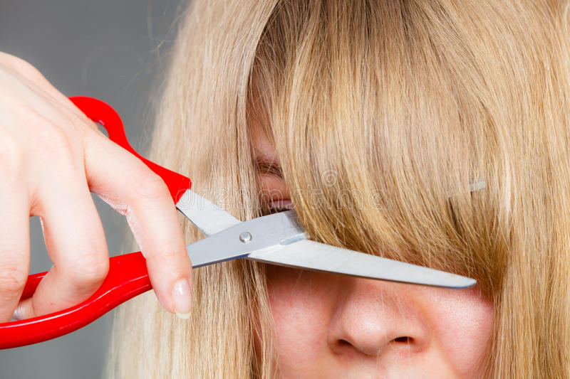 Woman cutting her fringe. Little look change concept. Young blonde woman cutting down shearing her fringe short front hair. Girl using big scissors royalty free stock photography
