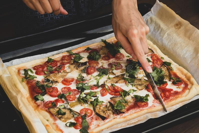 Woman cutting by knife rectangular shape and thick hand made romana`s pizza traditional italian pizza margherita closeup stock image