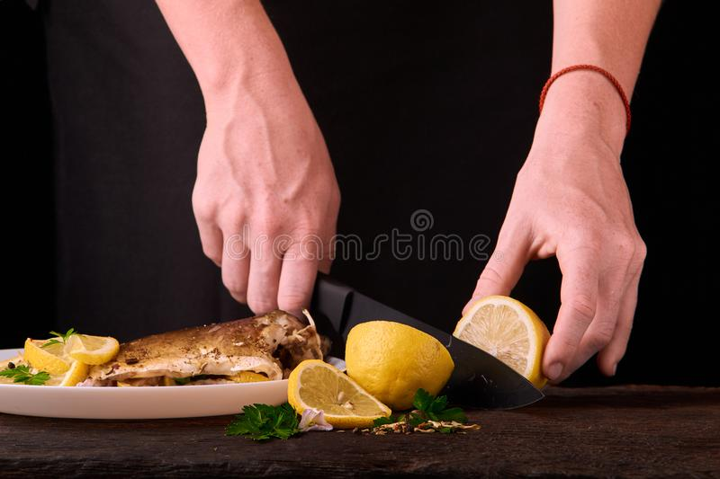 woman cutting lemon for baked fish on wooden board for dish in the kitchen, view of hands close-up. Cooked fish with lemon, spices royalty free stock image