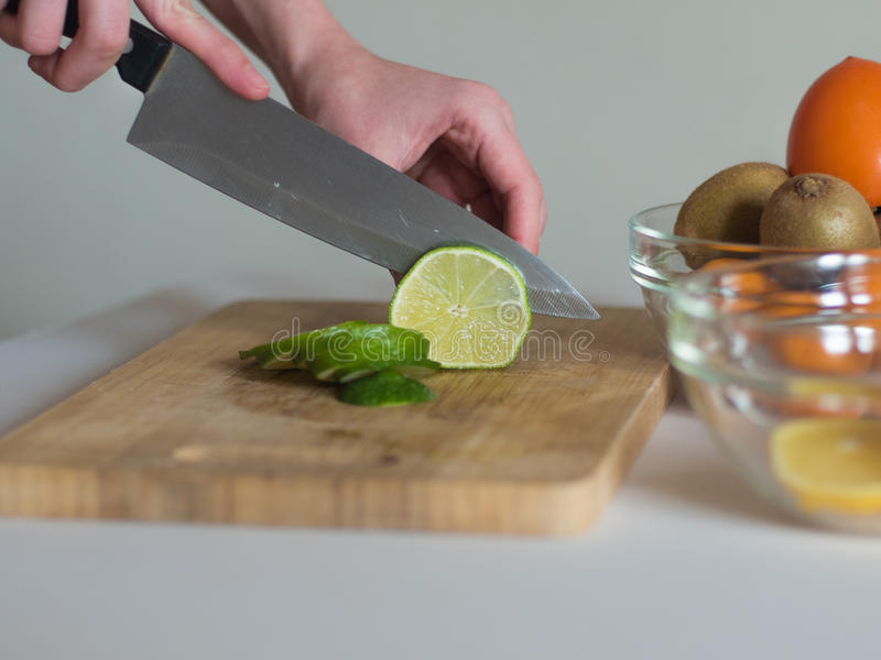 Woman cutting the lime on wooden board. Woman cutting the lime into thin pieces on wooden board for making a drink stock photo