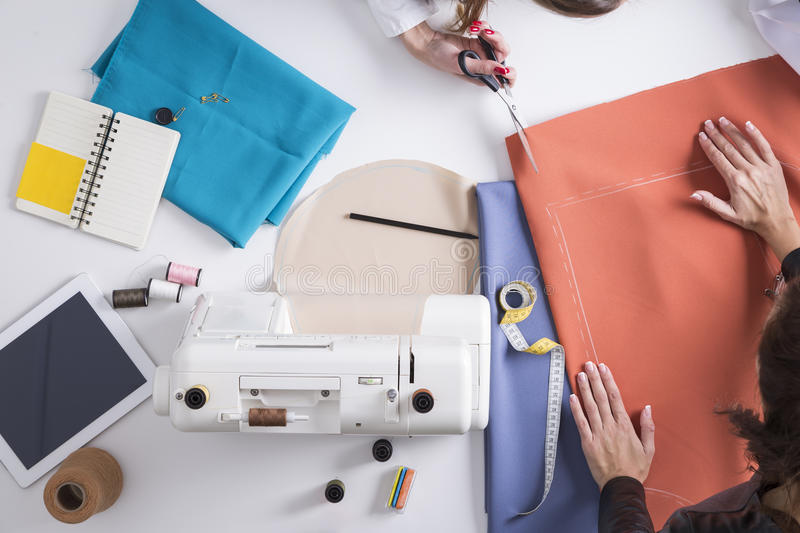 Woman cutting material her colleague is holding stock image