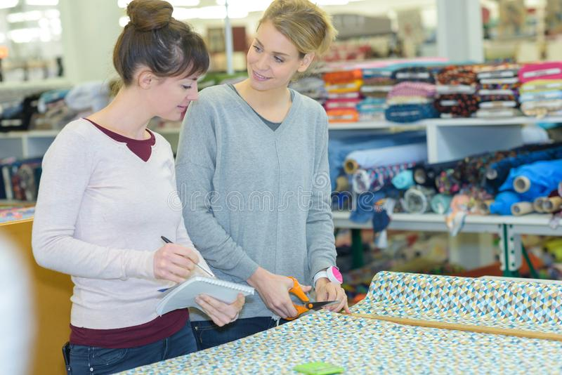 Woman cutting material in store. Woman royalty free stock image
