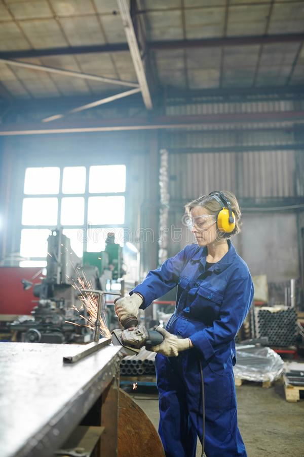 Woman Cutting Metal. Portrait of strong young woman cutting metal at industrial plant or garage stock photos