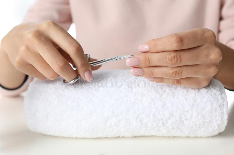 Woman cutting nails at table. At-home manicure stock photo