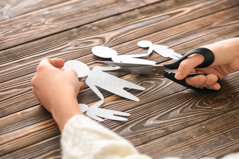 Woman cutting paper figures of family on wooden table. Concept of divorce stock photo