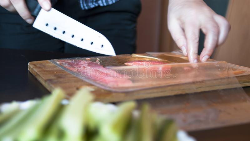 Woman Is Cutting Red Fish, Trout Fillet Packaged In Plastic Vacuum Pack On A Wooden Board. Hands Hold A Santoku Knife With Holes royalty free stock photos