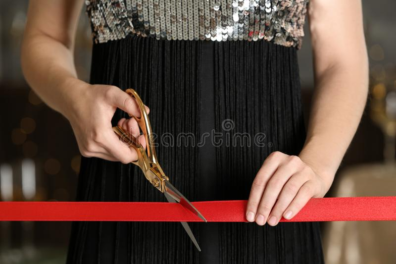 Woman cutting red ribbon with scissors at ceremonial event. Woman cutting red ribbon with scissors indoors at ceremonial event royalty free stock images