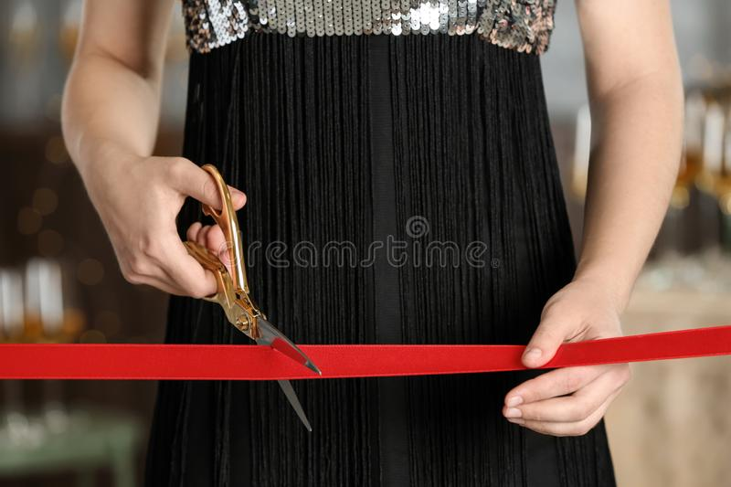 Woman cutting red ribbon with scissors at ceremonial event. Woman cutting red ribbon with scissors indoors at ceremonial event stock photography