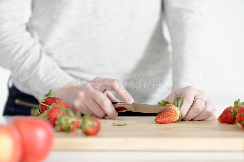 Woman cutting up fruit. Beautiful young woman preparing strawberries in her white kitchen stock image