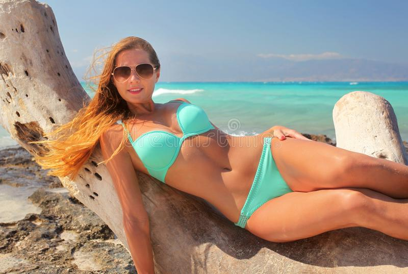 Woman in cyan blue bikini and sunglasses, laying on the drift wood tree, with turquoise sea behind her. royalty free stock photo