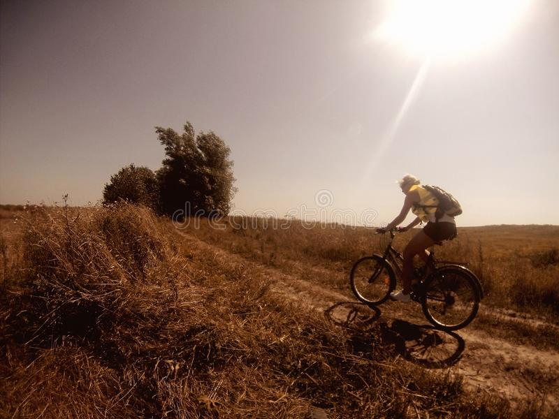 Woman cycling in countryside stock image