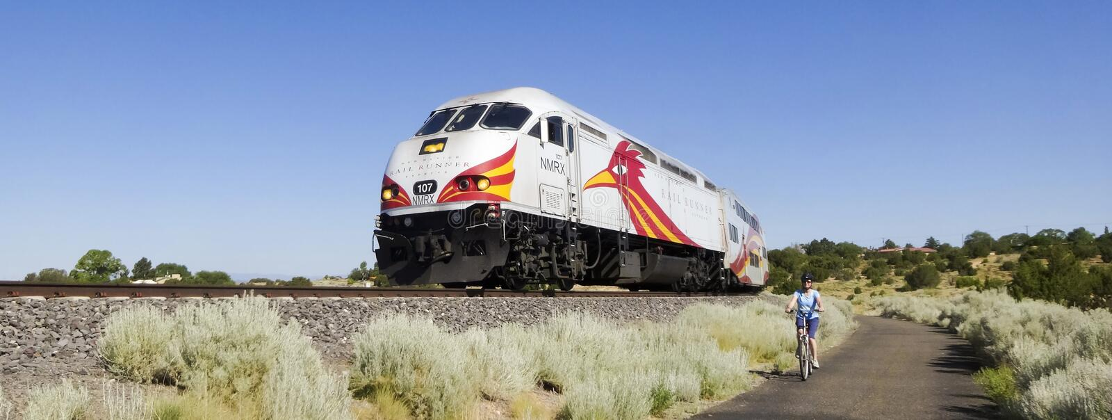 A Woman Cyclist Races the Rail Runner Express stock photo