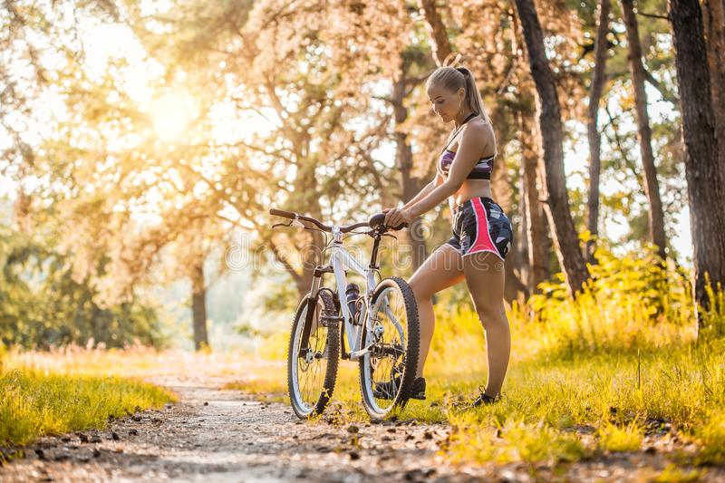 Cyclist resting under a tree and drinking water. Woman Cyclist resting under a tree and drinking water. Adventure travel royalty free stock image