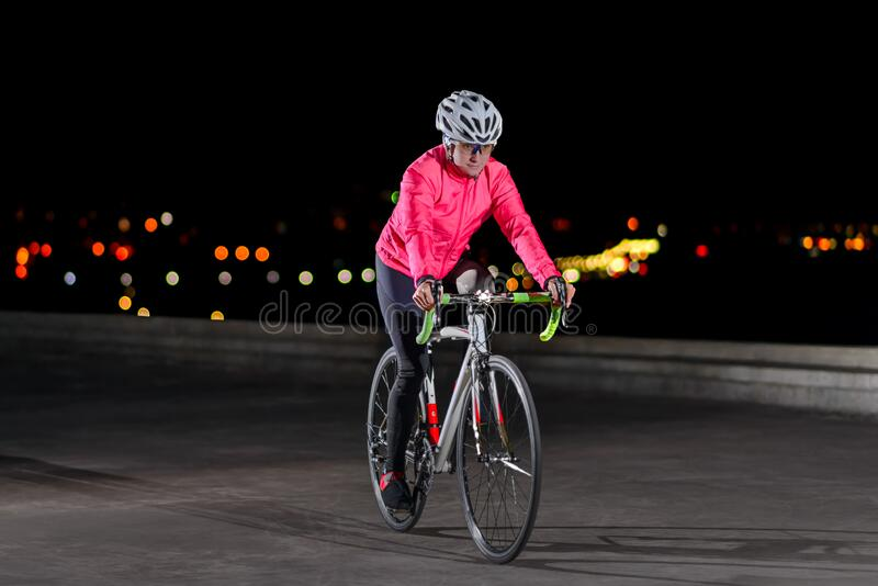 Woman Cyclist Riding Road Bike at Night in the City. Healthy Lifestyle and Urban Sport Concept royalty free stock photography