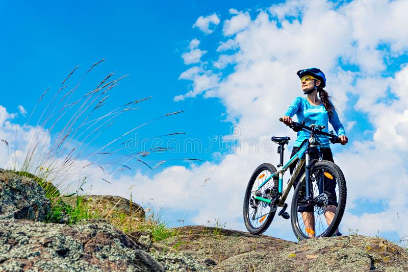 Woman cyclist stands on the hilltop with her mountain bike stock images