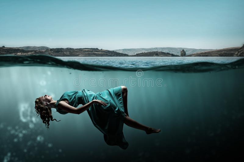 Woman dancer in clear blue water stock photos