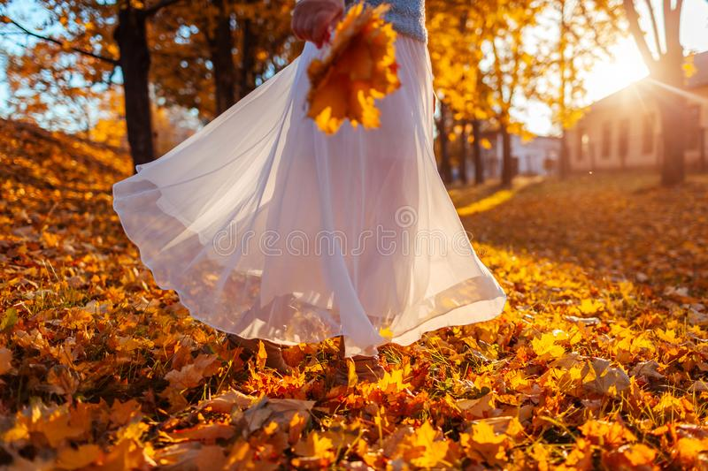 Woman dancing in autumn forest holding bouquet of yellow leaves. Lady wearing stylish white skirt stock images