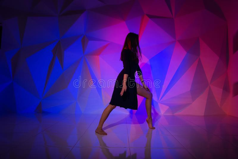 Woman dancing on the background of a beautiful multicolored wall. Sexy slim lonely girl with long black hair in a royalty free stock image