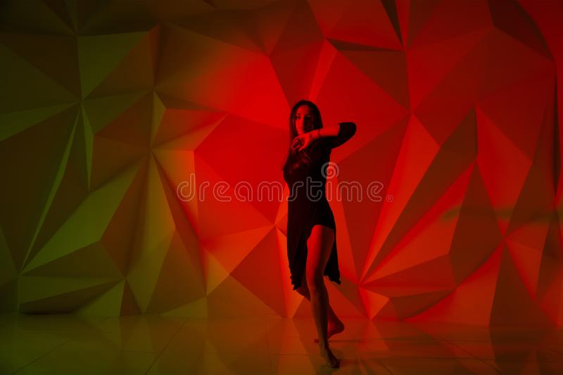 Woman dancing on the background of a beautiful multicolored wall. Sexy slim lonely girl with long black hair in a stock photo