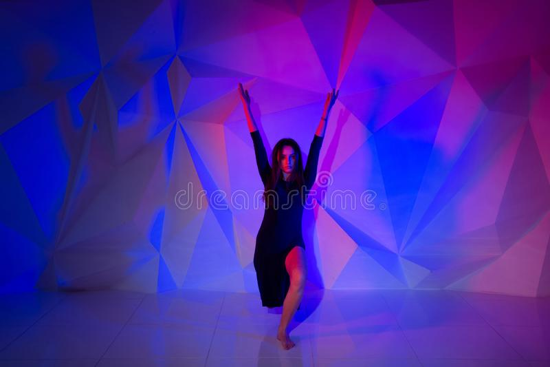 Woman dancing on the background of a beautiful multicolored wall. Sexy slim lonely girl with long black hair in a stock photos