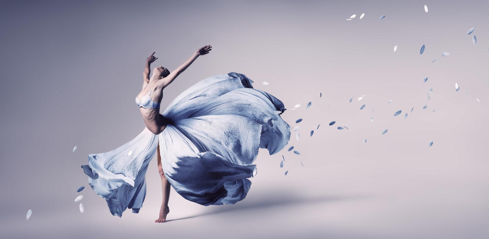 Woman dancing in flowing blue dress stock images