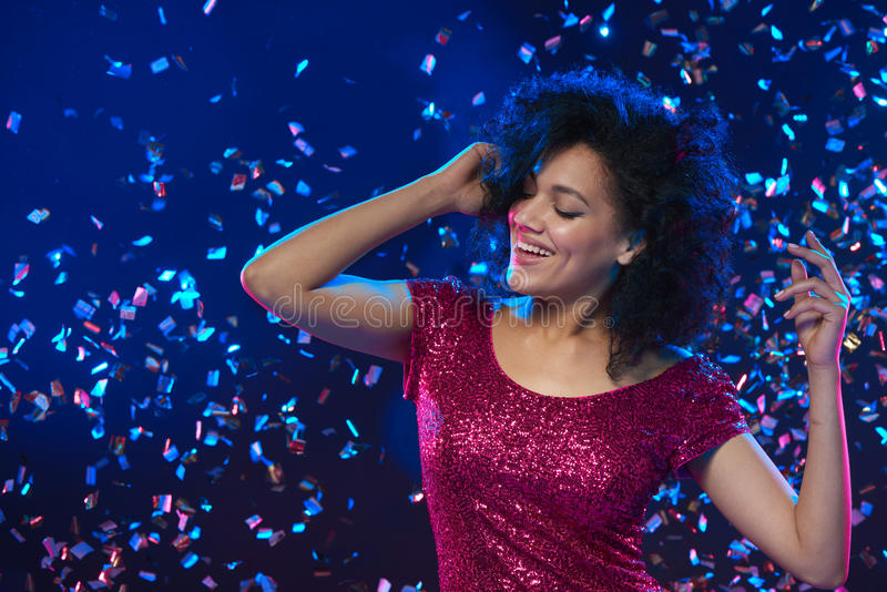Woman dancing on a party over colorful background with confetti. Closeup of happy mixed race woman in sequined dress dancing on a party over colorful background royalty free stock photo