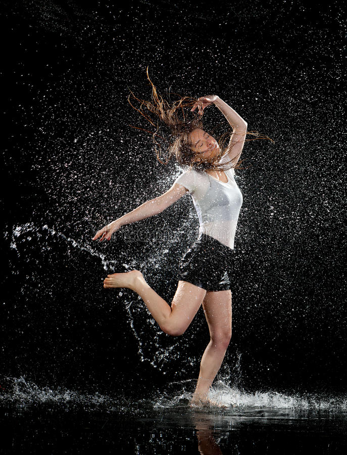Woman dancing rain black background royalty free stock images