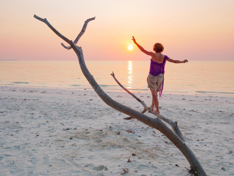Woman dancing on sand beach romantic sky at sunset, rear view silhouette, golden sunlight, real people. Indonesia, Kei islands, stock photo
