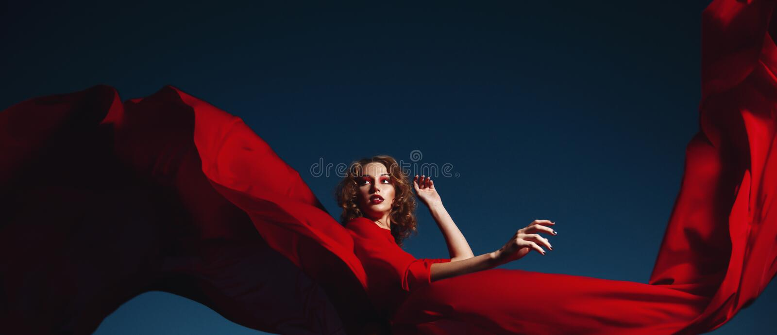 Woman dancing in silk dress, artistic red blowing gown waving and flittering fabric. In the night stock photography