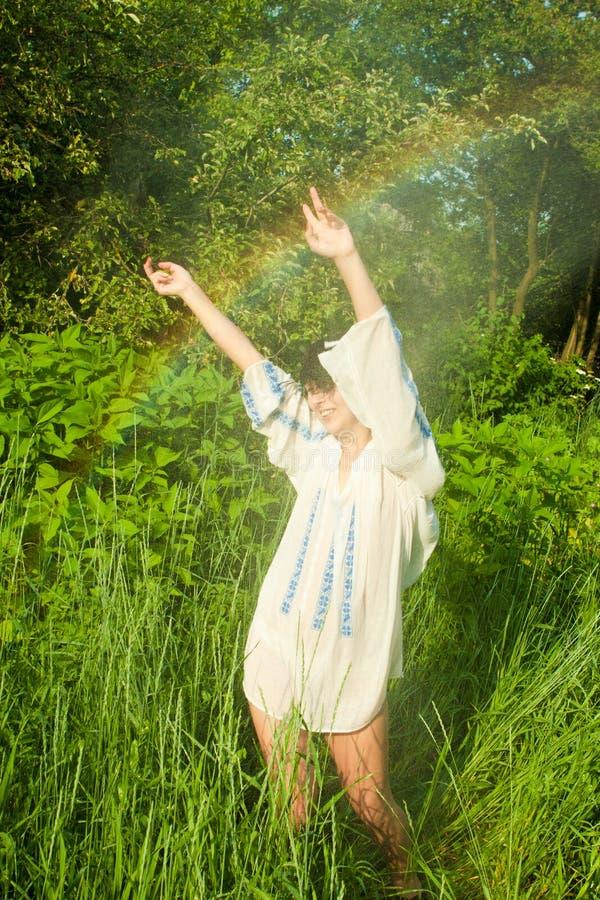 Woman dancing in summer rain. Young woman in ethnic blouse dancing in sunny summer rain stock images