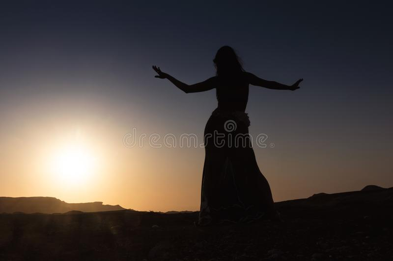 Woman dancing to the famous Arab belly dance. With sunset in the arid desert plain of Namibe. Africa. Angola stock photos