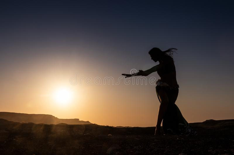 Woman dancing to the famous Arab belly dance. With sunset in the arid desert plain of Namibe. Africa. Angola royalty free stock photography