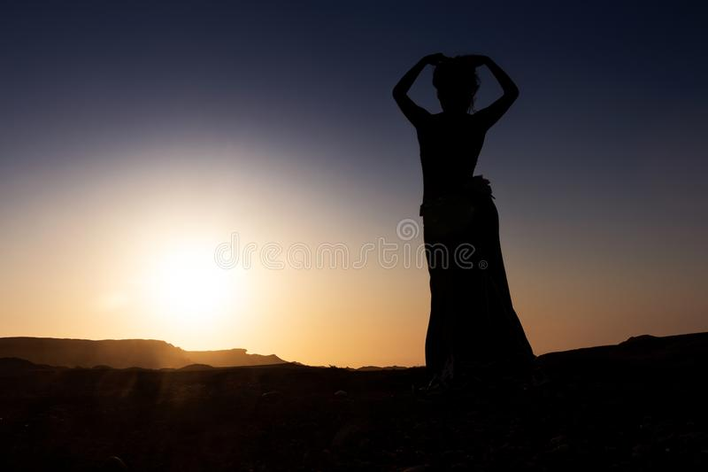 Woman dancing to the famous Arab belly dance. With sunset in the arid desert plain of Namibe. Africa. Angola stock photo