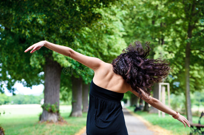 Woman dancing and turned back. In the park with fluttered hair stock images