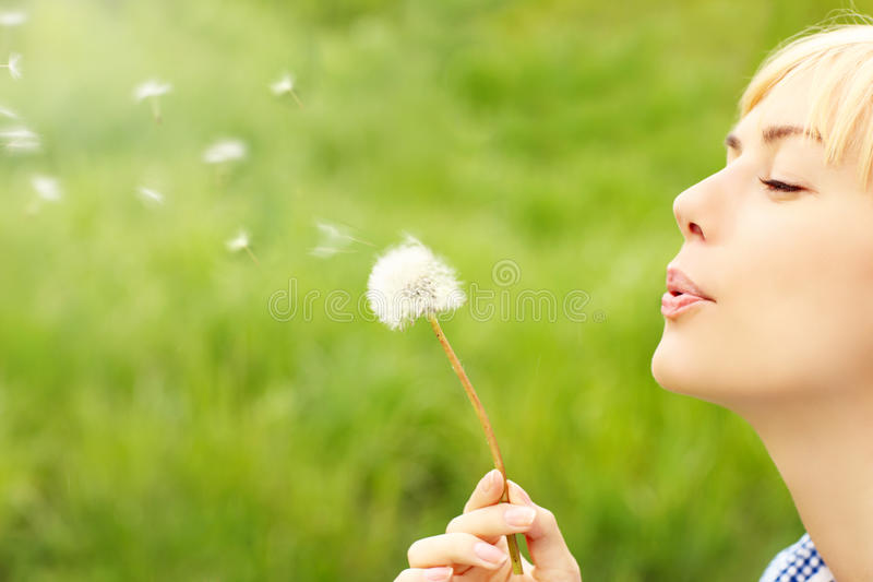 Woman with dandelion. A picture of a woman blowing a dandelion over green background royalty free stock photos