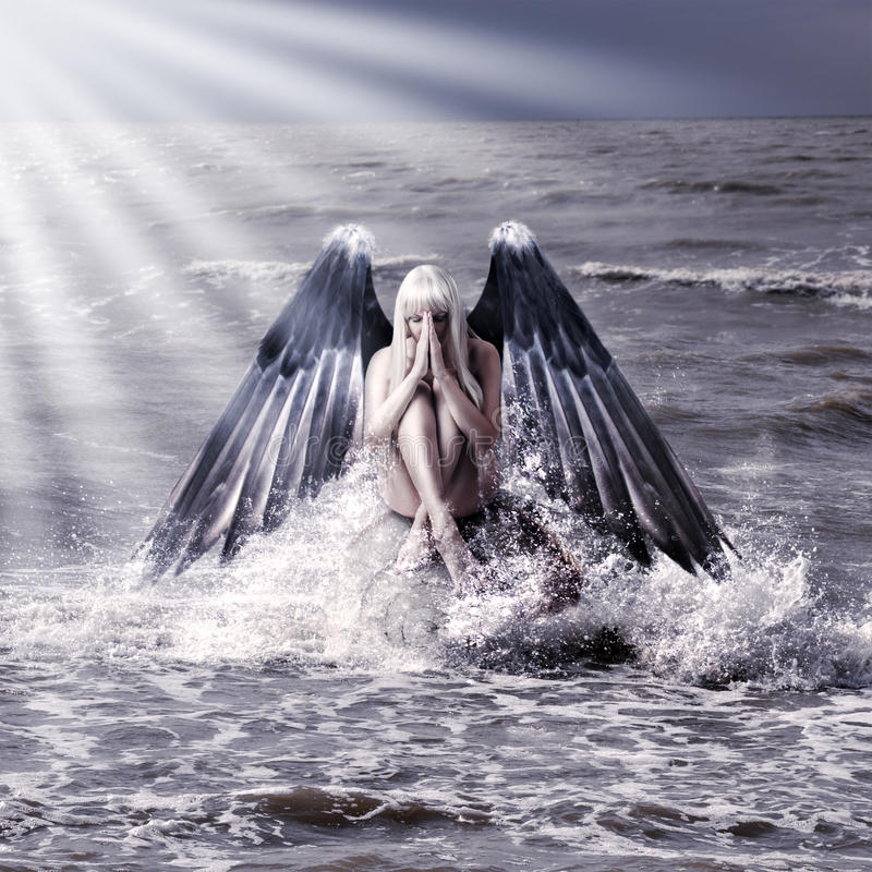 Woman with dark angel wings. Fantasy portrait of woman with dark angel wings praying while sitting in spray of sea during storm