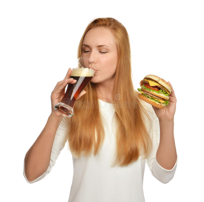 Woman with dark beer mug and burger sandwich hamburger. Happy young woman with dark beer mug and burger sandwich hamburger in hands hungry drinking isolated on a royalty free stock images
