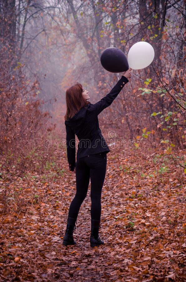 Woman in dark clothing in autumn foggy forest, with two balloons, black and white. Concept of choice, good and evil stock photo