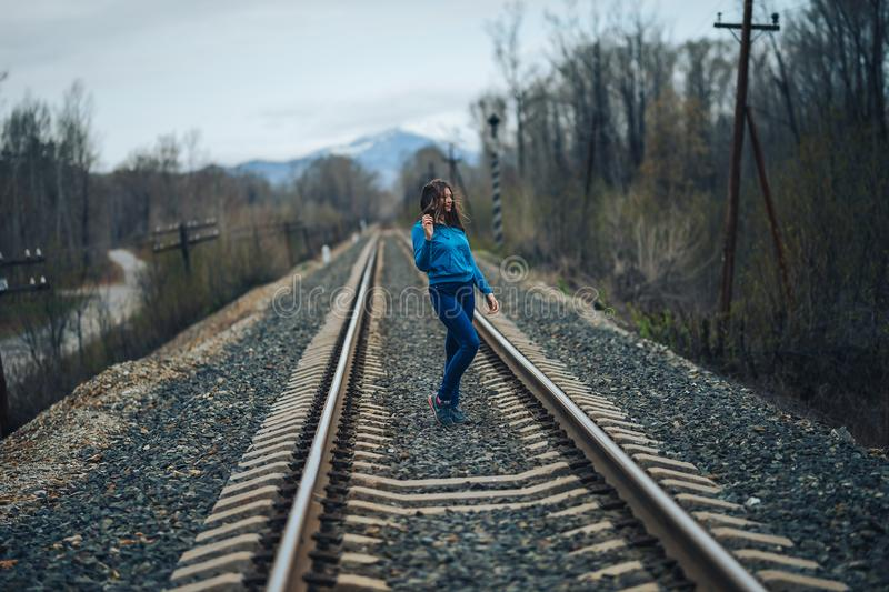 Woman with dark hair standing on railway track, wind in hair stock photography