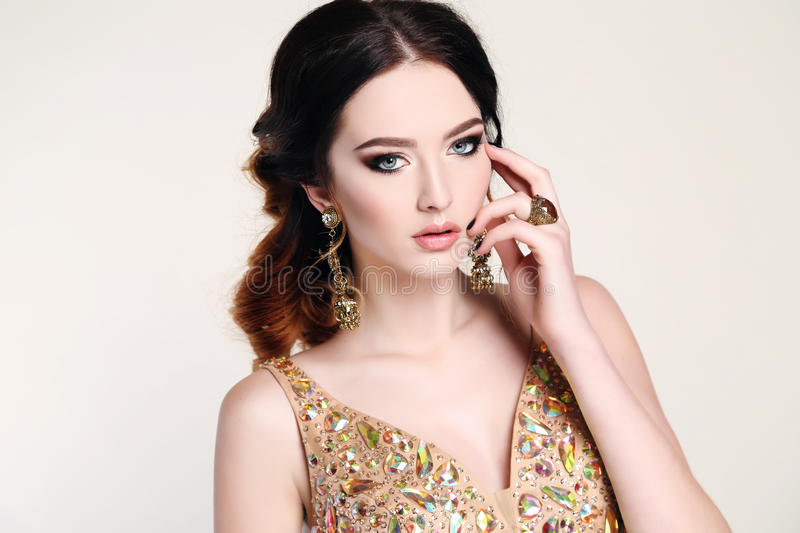 Woman with dark hair wearing luxurious sequin dress and bijou. Fashion studio photo of beautiful sensual woman with dark hair wearing luxurious sequin dress and stock photography